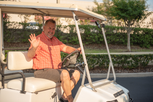 Member of Team Mainstreet driving golf cart during Clermont's 2nd anniversary celebration