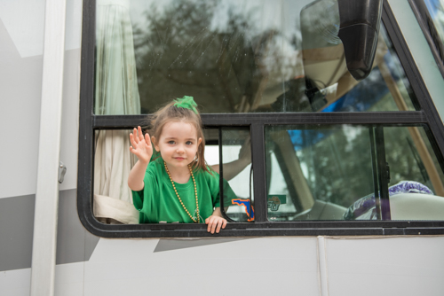 A little girl waving out the window of the Mainstreet Community Bank RV during the Mardi Gras dog parade
