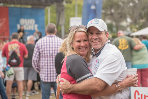 Man and woman hugging during Pig on the Pond event in Clermont