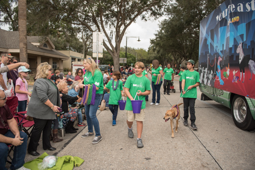 Team Mainstreet handing out candy along the parade route at the Mardi Gras dog parade in DeLand