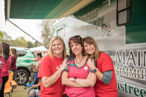 A group of ladies smiling for a photo in front of the Mainstreet RV at Pig on the Pond