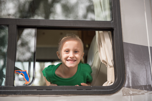 A little girl smiling from the window of the Mainstreet Community Bank RV before the Mardi Gras on Mainstreet Parade