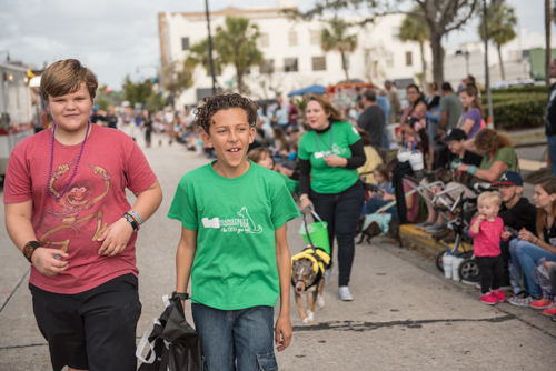 Two boys smiling while walking in the Mardi Gras dog parade in DeLand