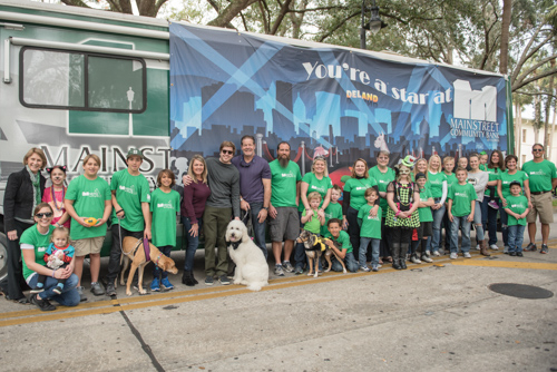 Group portrait of Team Mainstreet in front of the Mainstreet RV before the Mardi Gras on Mainstreet Parade