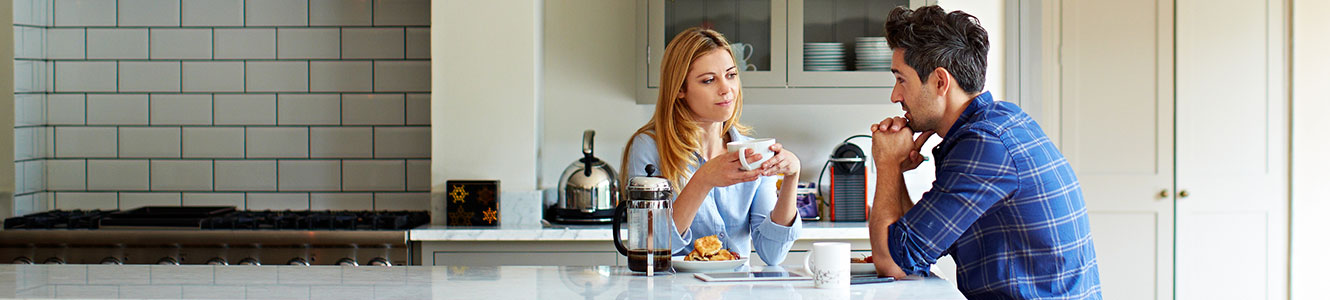 Young couple drinking coffee in their kitchen.