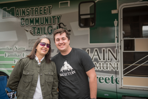 Mother and adult son posing for photo in front of Mainstreet Community Bank RV at Pig on the Pond