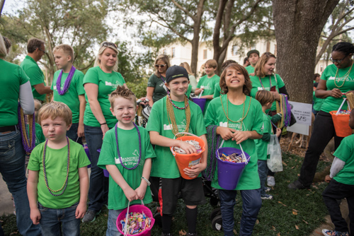 A group of kids smiling with buckets of candy to hand out at the Mardi Gras dog parade in DeLand