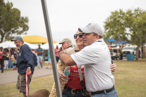 Team Mainstreet members greeting each other with a hug at Pig on the Pond event in Clermont