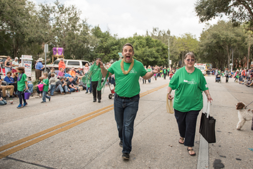 Team Mainstreet handing out beads along the parade route at the Mardi Gras dog parade in DeLand