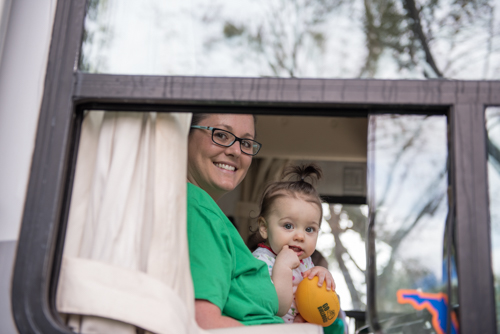 A mom and her daughter smiling from the window of the Mainstreet Community Bank RV before the Mardi Gras dog parade in DeLand