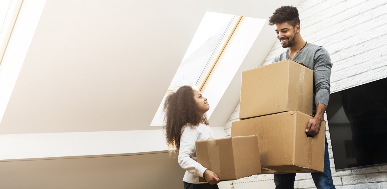 Man and child moving boxes in house
