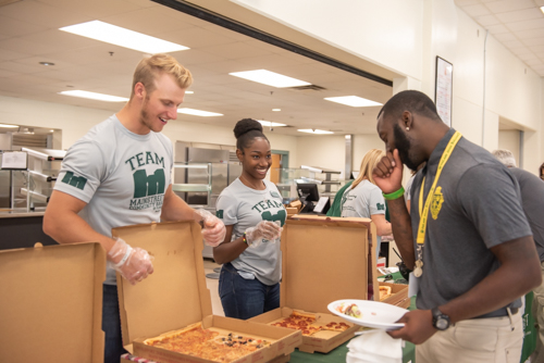 A man and woman serve a DeLand High School teacher lunch of pizza and wings