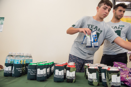 Sodas in Mainstreet Community Bank coozies sitting on a table as two young men line up chips at DeLand High School