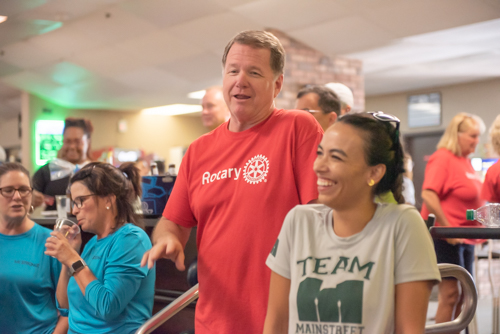 A man and woman laugh while other people chat in background at Bowling for Literacy event in DeLand
