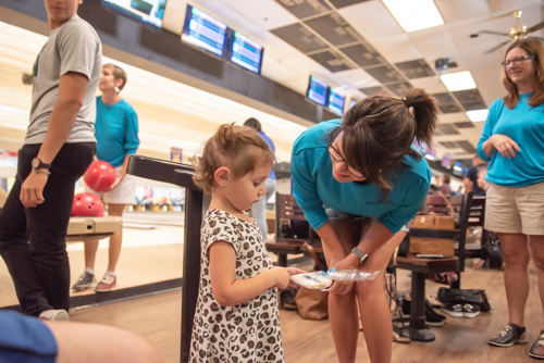 A woman gives a little girl a cookie at bowling alley