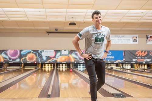 Man walking away from bowling lane with hands on hips