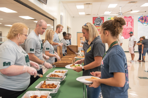 Teachers select food from the table while members of Team Mainstreet assist at DeLand High School