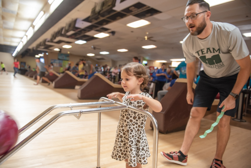 A little girl bowls while her father encourages her at Bowling for Literacy Event in DeLand, FL
