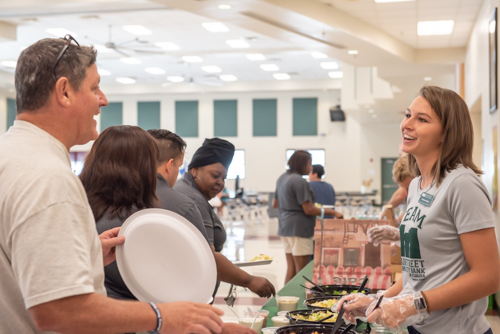 A woman smiles and greets a teacher during the DeLand High School teacher lunch hosted by Mainstreet Community Bank