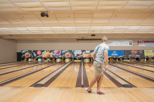 Man watches bowling ball roll towards pins at bowling alley in DeLand, FL