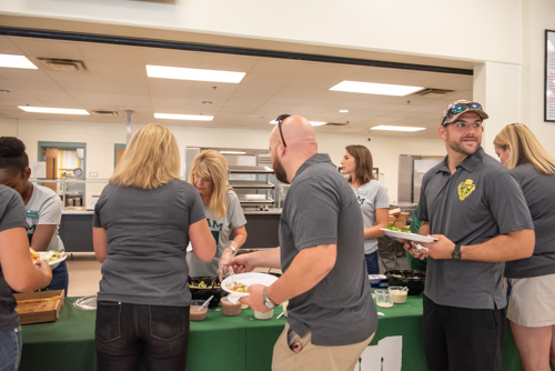 A male teacher looks on as other teachers get lunch from members of Team Mainstreet at DeLand High School