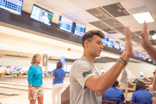 Man gives high five after his turn at bowling alley