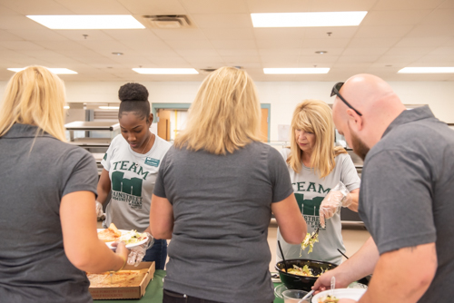 Two Mainstreet Community Bank employees serve teachers salad and pizza during lunch at DeLand High School