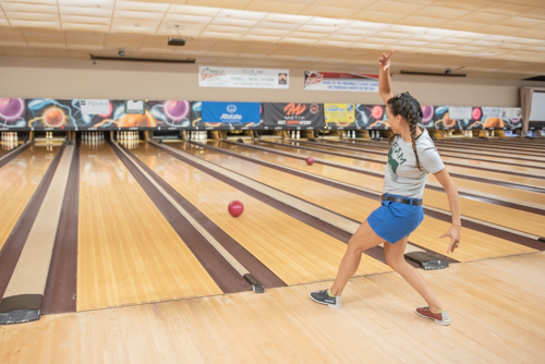 A woman bowls in a comical way during Bowling for Literacy event.