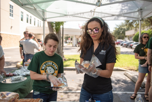 Mainstreet Team Members wrap hotdogs during Customer Appreciation Day