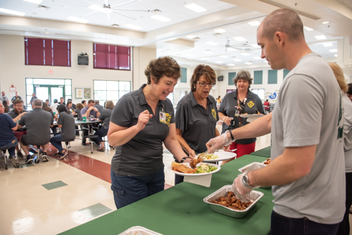 A man serves chicken wings to a teacher as other teachers eat lunch in the background at DeLand High School