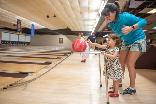 A woman helps a little girl bowl during Bowling for Literacy event in DeLand FL