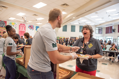 A teacher excitedly grabs a man who is a former student while serving lunch for the staff of DeLand High School