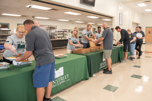 A group of Mainstreet Community Bank employees serve lunch to teachers at DeLand High School.