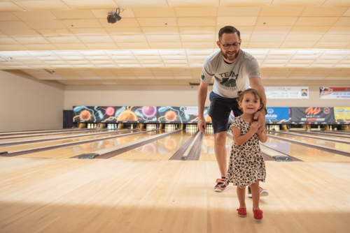 Little girl leads her father away from bowling lane after bowling with him