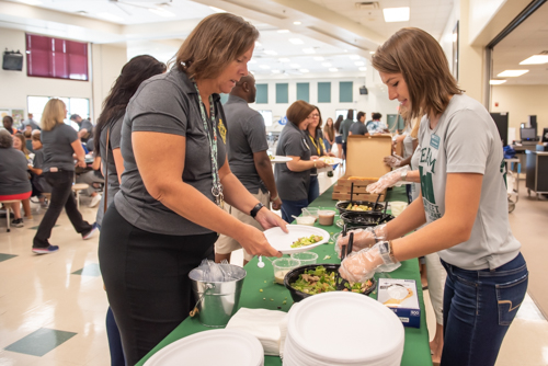 A Mainstreet Community Bank employee serves salad to a teacher while others eat lunch in the cafeteria of DeLand High School