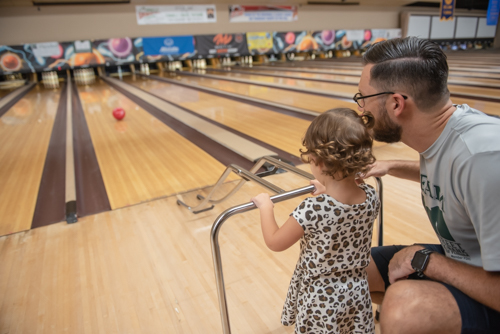 Little girl and father using bowling bar to play at bowling alley