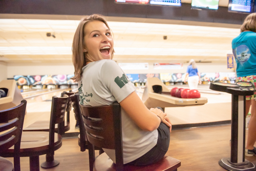 A woman sitting in a chair laughs while people in background bowl at bowling alley